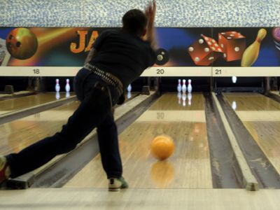 A bowler throws his bowling bowl down the lane